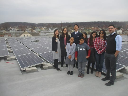 Paterson School 9 students with science teachers Jeanne Albanese, far left, and Carlos Miranda, far right, up on the roof near solar panels installed as part of the first phase of the Paterson Public Schools Energy Savings Improvement Project.