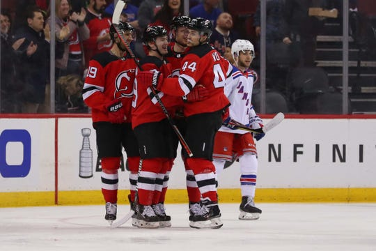 The New Jersey Devils celebrate a goal by New Jersey Devils left wing Miles Wood (44) during the first period of their game against the New York Rangers at Prudential Center.