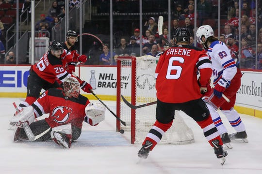 New Jersey Devils defenseman Damon Severson (28) pulls the puck off the goal line behind New Jersey Devils goaltender Mackenzie Blackwood (29) during the first period of their game against the New York Rangers at Prudential Center.