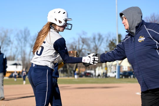 Rutherford's Jordan Finelli, left, high-fives head coach Helen Antzoulides as they play extra innings against Saddle Brook on Monday, April 1, 2019. Rutherford defeated Saddle Brook in an 11-10 walk-off win for the first game of the season.
