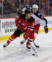 Mar 5, 2019; Newark, NJ, USA; New Jersey Devils left wing Jesper Bratt (63) plays the puck against Columbus Blue Jackets defenseman Zach Werenski (8) during the second period at Prudential Center.