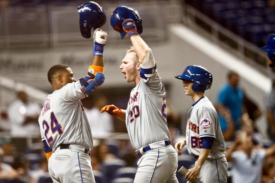 New York Mets' Pete Alonso (20) celebrates with teammate Robinson Cano (24) after hitting a three-run home run during the ninth inning of a baseball game against the Miami Marlins, Monday, April 1, 2019, in Miami. (AP Photo/Brynn Anderson)