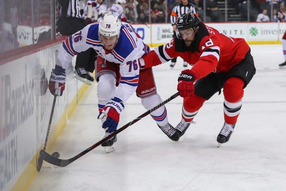 April 1, 2019; Newark, NJ, USA; New York Rangers defenseman Brady Skjei (76) and New Jersey Devils right wing Drew Stafford (18) battle for the puck during the first period at Prudential Center. Mandatory Credit: Ed Mulholland-USA TODAY Sports