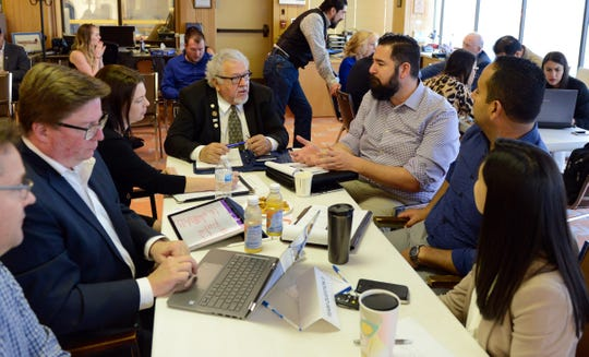"Doña Ana County Commissioner Ramon Gonzalez (center in glasses) speaks to members of his team during Dell's ""policy hack"" on Tuesday, April 2 in Santa Teresa."