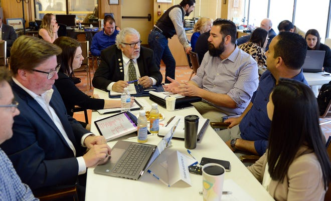 """Doña Ana County Commissioner Ramon Gonzalez (center in glasses) speaks to members of his team during Dell's """"policy hack"""" on Tuesday, April 2 in Santa Teresa."""