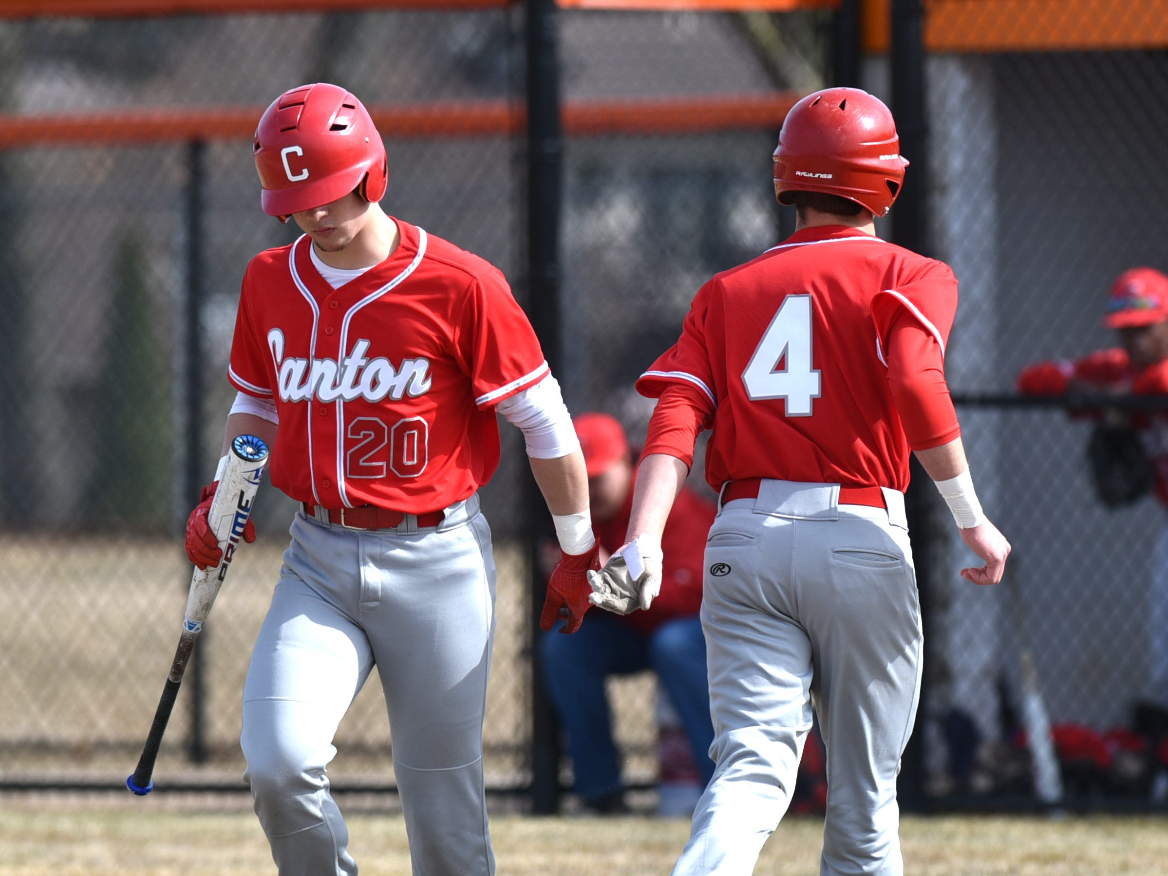 Canton Chief Marco Johnson, left, congratulates Ben Stayziak after he'd brought in a run on a bases loaded walk.