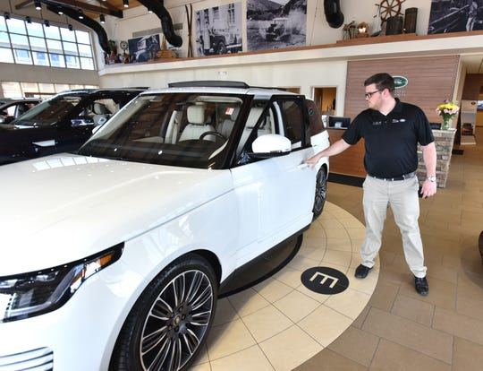 Jaguar and Land Rover of Farmington Hills' salesman Aric Wilson opens up the door of a 2019 Range Rover at the Grand River Ave. dealership. The auto sales center will soon move to a new location in Novi.