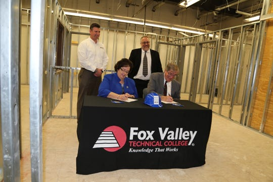 Fox Valley Technical College President Susan May and Concordia University Wisconsin Provost William Cario sign a partnership agreement Tuesday, April 2, 2019, at the S.J. Spanbauer Training Center in Oshkosh. The deal will allow FVTC graduates to earn a bachelor's degree in construction and trades management through Concordia.