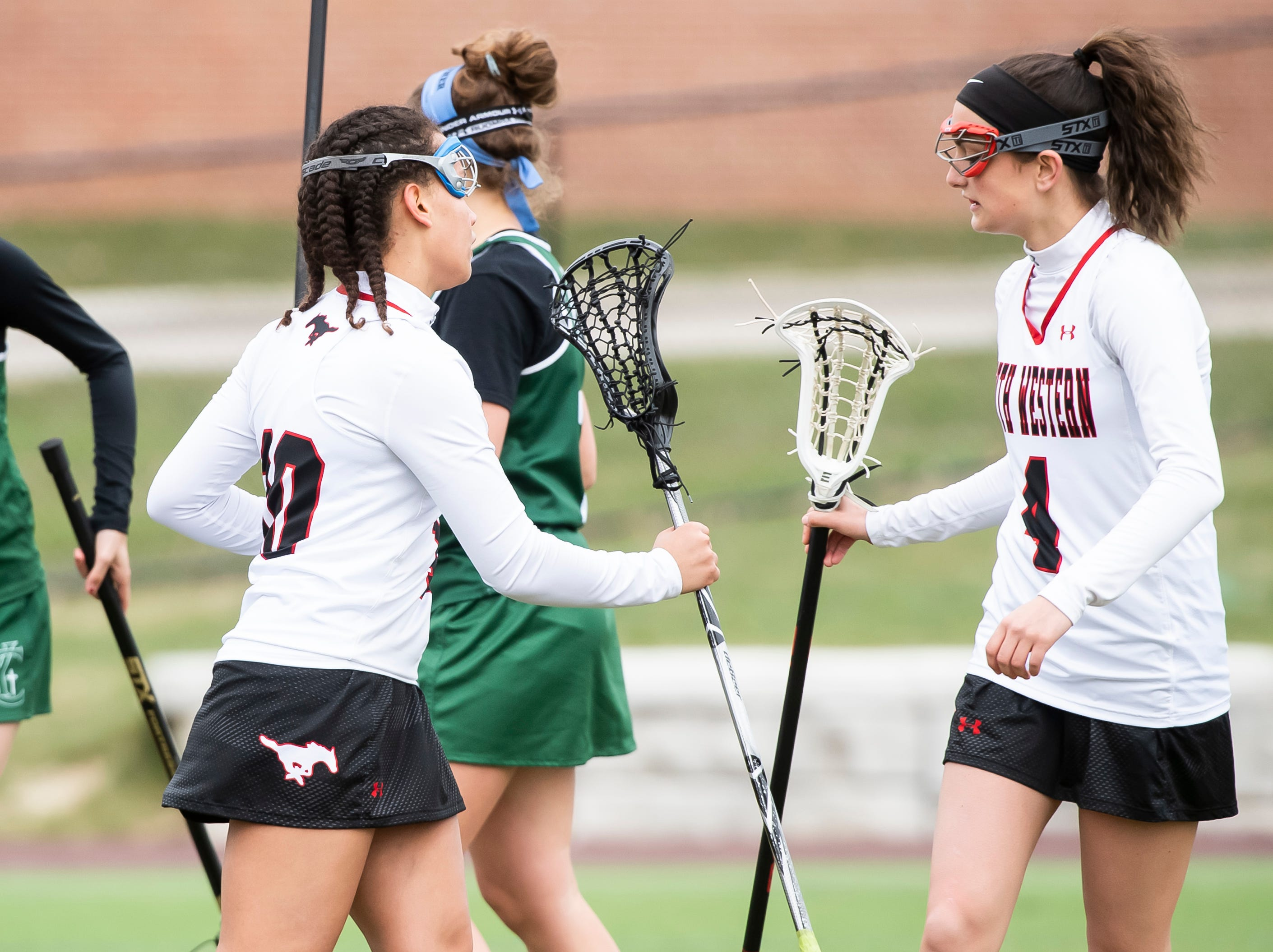 South Western's Caitlyn Coates and Ella Baker (4) tap sticks after Coates scored a goal during a YAIAA lacrosse game against York Catholic on Tuesday, April 2, 2019. South Western fell 19-7.