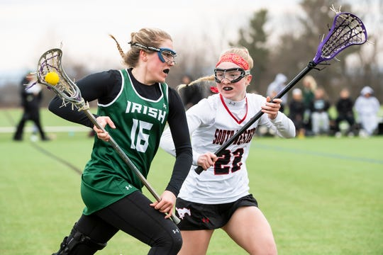 York Catholic's Grace Reed (16) races downfield against South Western's Aunnie Hacker (22) during a YAIAA lacrosse on Tuesday, April 2, 2019. York Catholic won 19-7 and improved to 5-0.