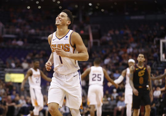 Suns' Devin Booker (1) laughs as he jogs up the court after hitting a three pointer against the Cavaliers during the second half at Talking Stick Resort Arena in Phoenix, Ariz. on April 1, 2019.