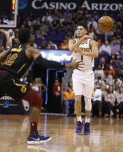 Suns' Devin Booker (1) passes the ball against the defense of Cavaliers' David Nwaba (12) during the first half at Talking Stick Resort Arena in Phoenix, Ariz. on April 1, 2019.