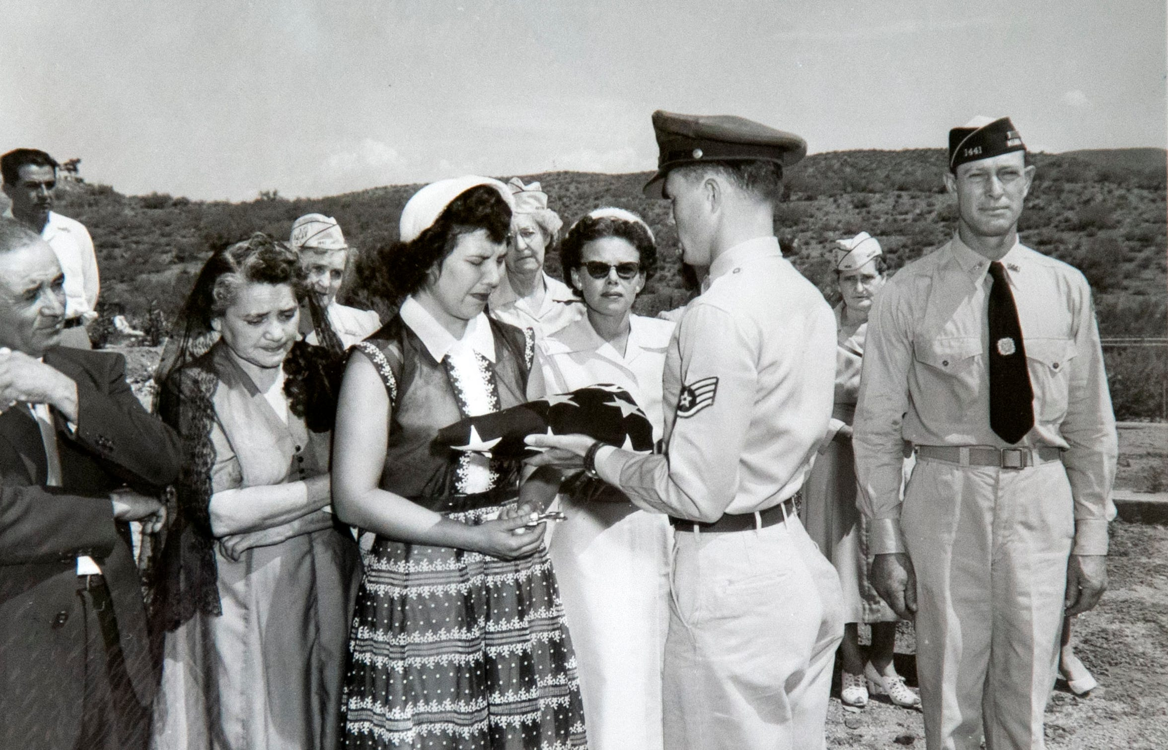 Jovita Campos receives a folded American flag during the funeral service for her husband, Staff Sgt. Joe Campos, in Miami, Ariz., in July of 1953. Campos, a gunner on a B-26 bomber was likely the first American killed in the Korean War when his plane went down in the Yellow Sea on June 28, 1950. It took nearly three years for his remains to be found and identified so he could receive a proper burial.
