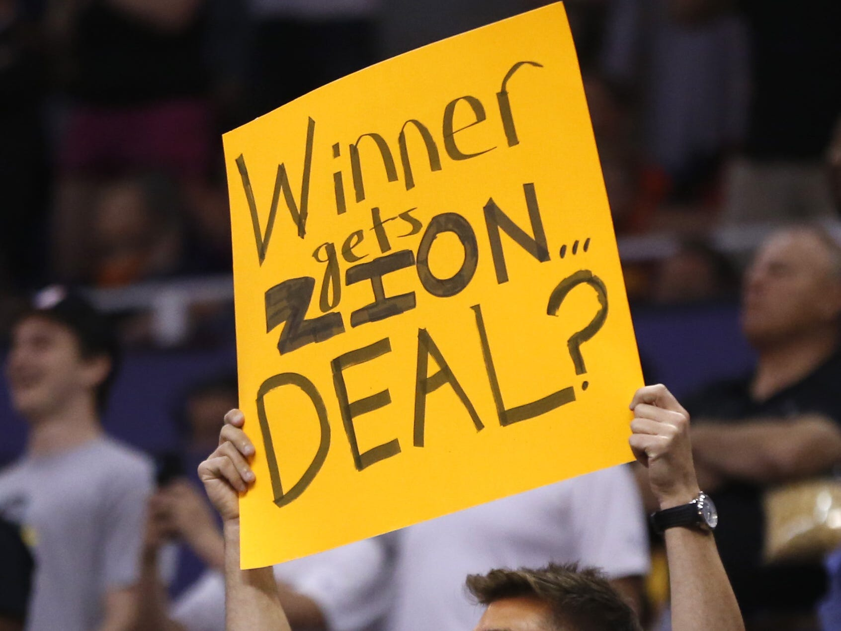 "A fan holds up a sign saying ""Winner gets Zion... Deal?"" during the first half at Talking Stick Resort Arena in Phoenix, Ariz. on April 1, 2019."