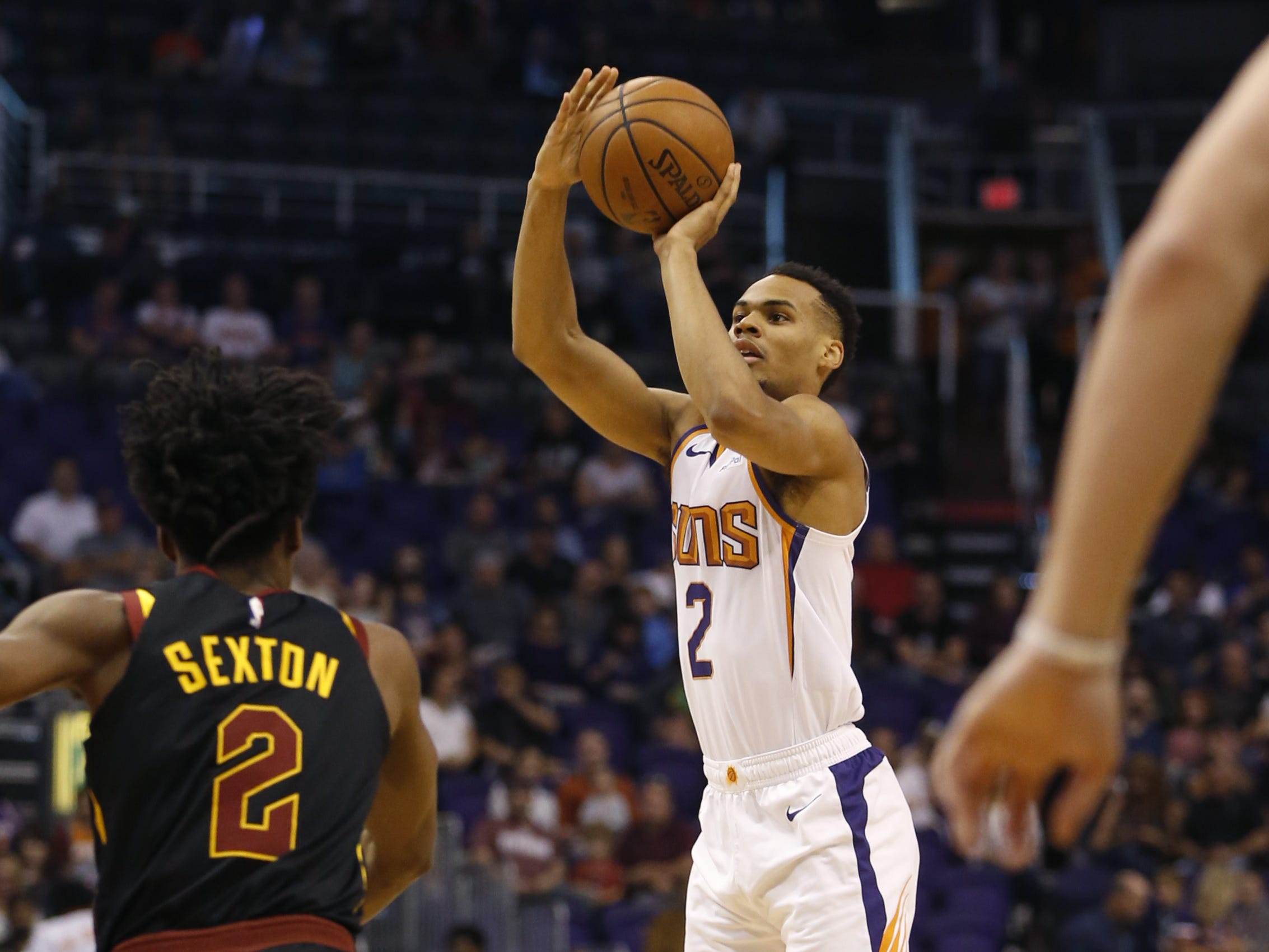 Suns' Elie Okobo (2) hits a three pointer against Cavaliers' Collin Sexton (2) during the first half at Talking Stick Resort Arena in Phoenix, Ariz. on April 1, 2019.