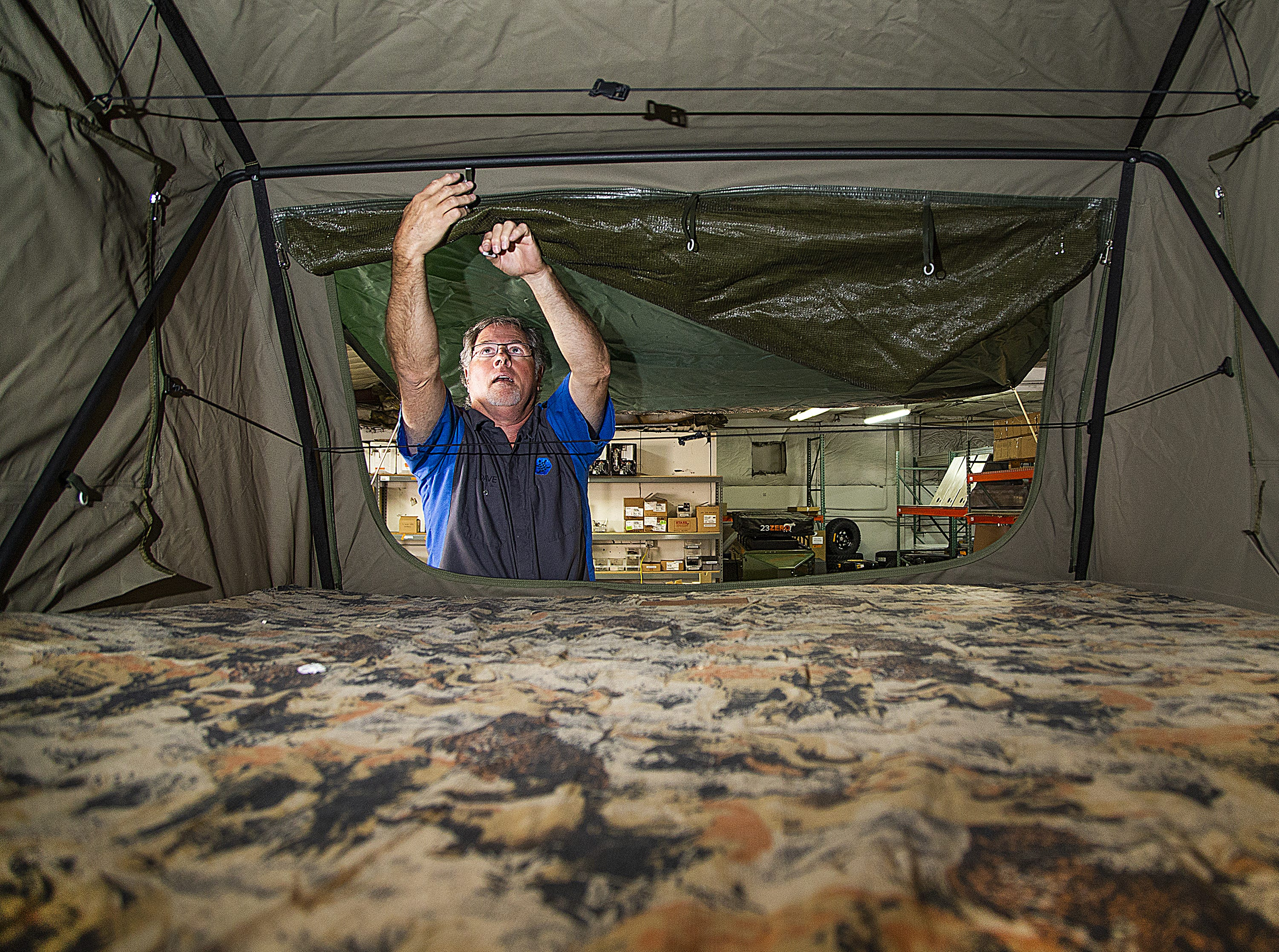Dave Munsterman adjusts the screen of the tent on top of a Turtleback trailer at the company plant near 14th Street and Broadway in Phoenix on March 26, 2019.