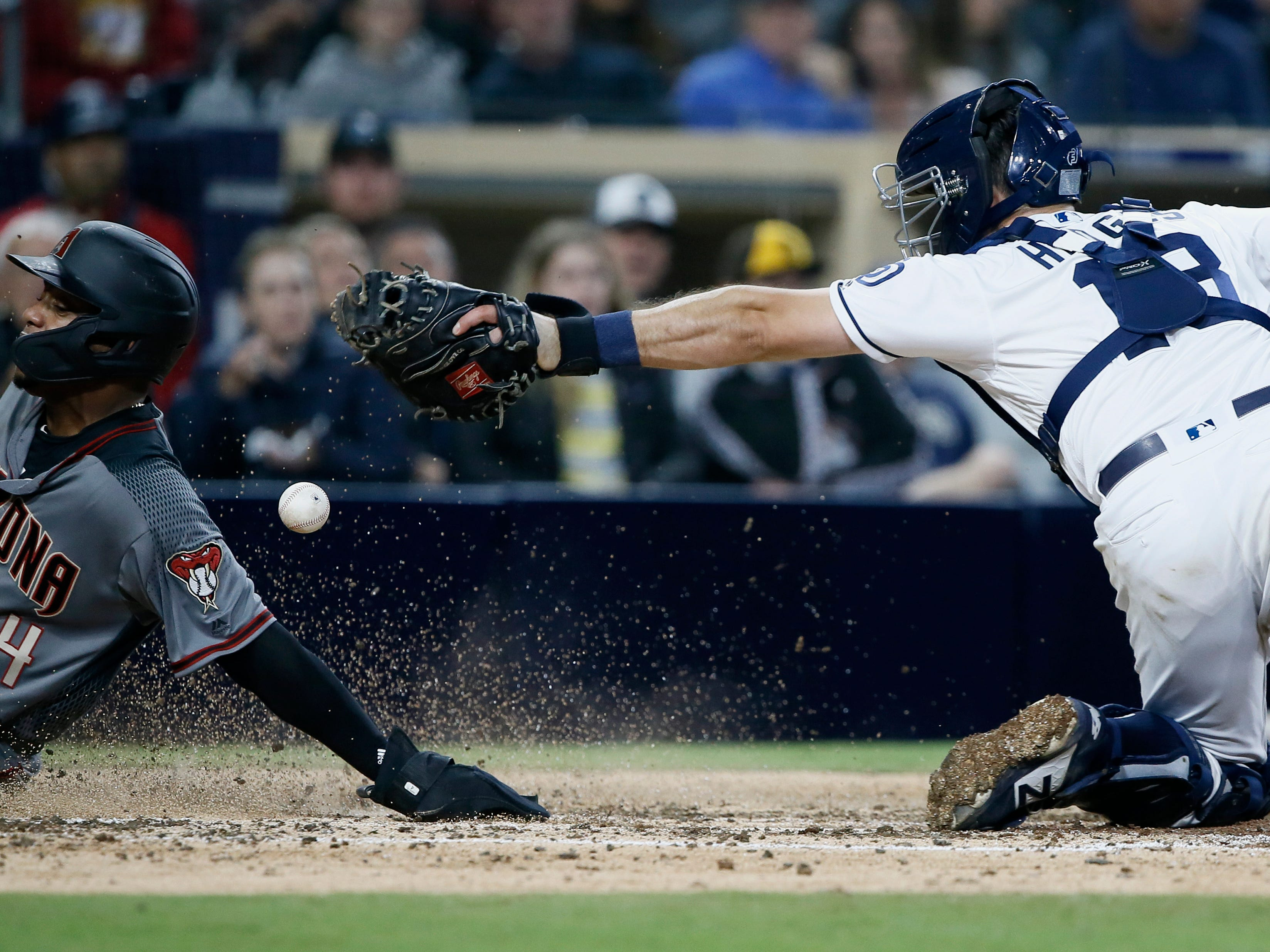 Arizona Diamondbacks' Ketel Marte, left, scores as San Diego Padres catcher Austin Hedges loses the ball on the tag during the fifth inning of a baseball game in San Diego, Monday, April 1, 2019. (AP Photo/Alex Gallardo)