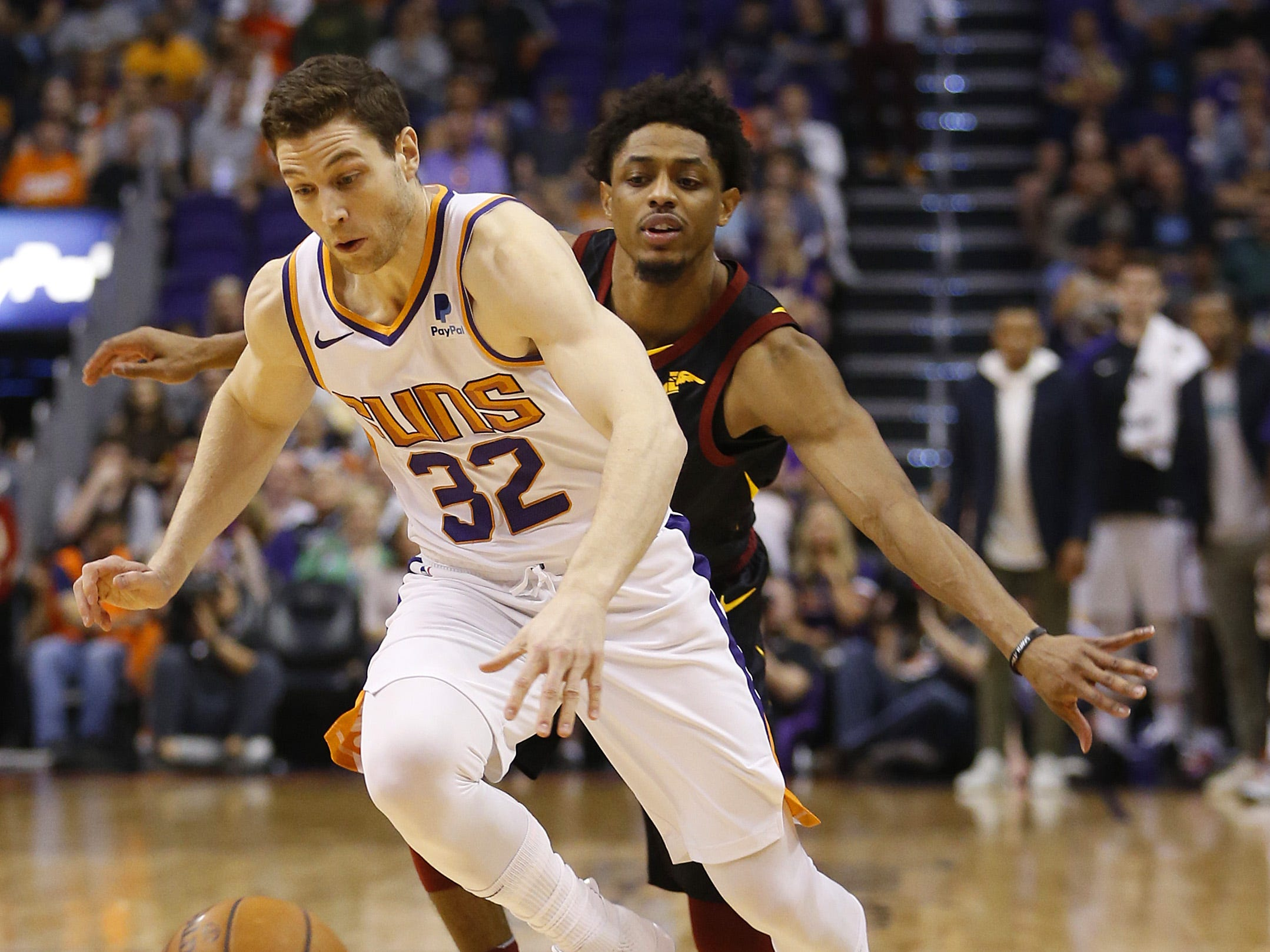 Suns' Jimmer Fredette (32) drives past Cavaliers' Brandon Knight (20) during the first half at Talking Stick Resort Arena in Phoenix, Ariz. on April 1, 2019.