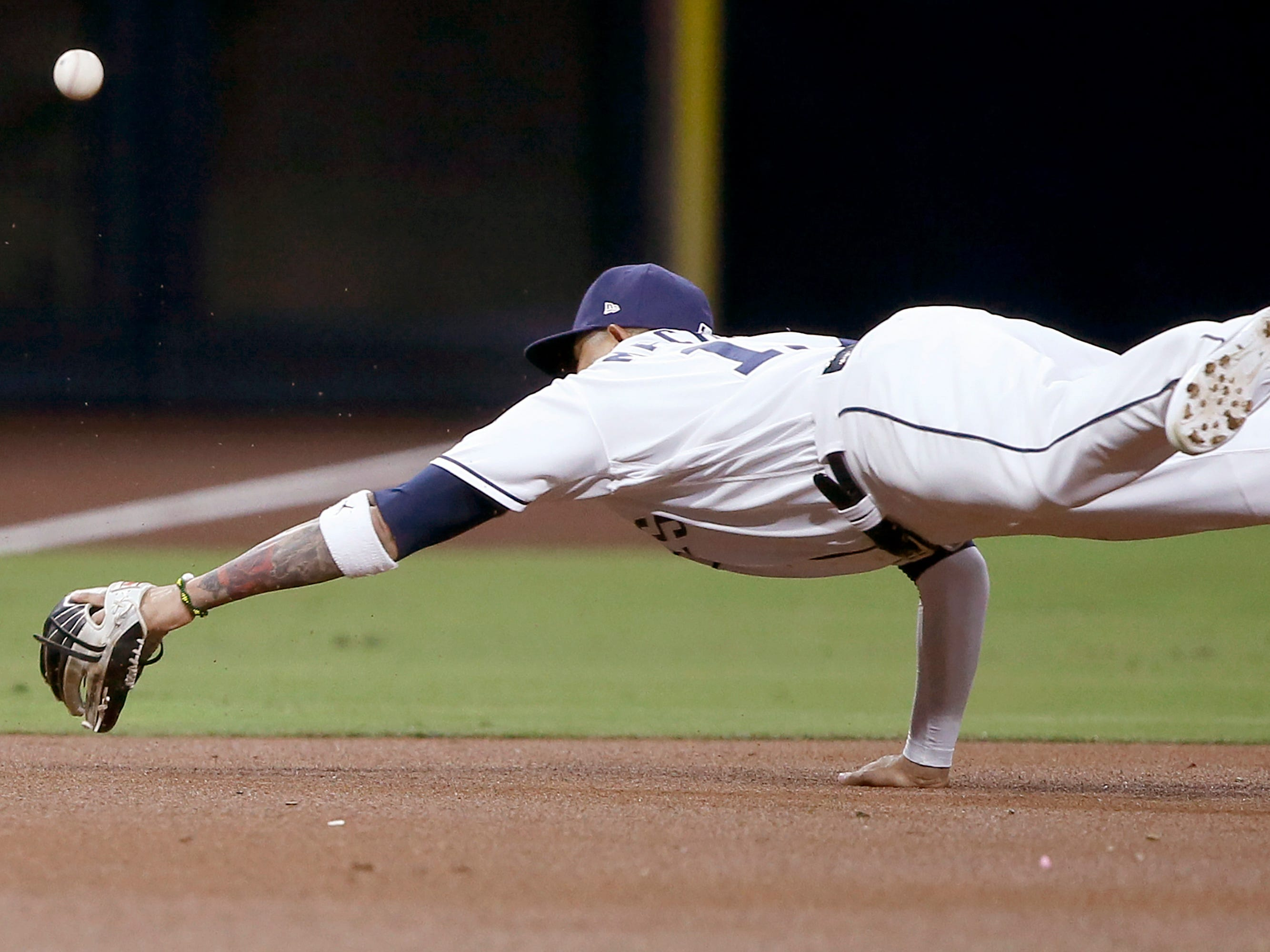 San Diego Padres third baseman Manny Machado dives for but cannot catch a single by Arizona Diamondbacks' Eduardo Escobar during the first inning of a baseball game in San Diego, Monday, April 1, 2019.