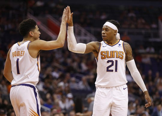Suns' Devin Booker (1) high-fives Richaun Holmes (21) after he found him for a dunk during the second half against the Cavaliers at Talking Stick Resort Arena in Phoenix, Ariz. on April 1, 2019.