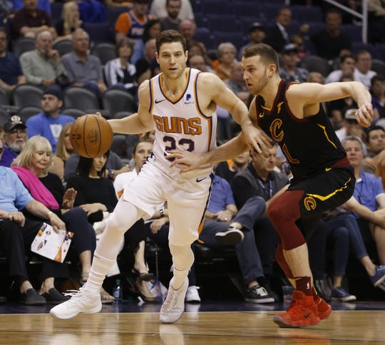 Suns' Jimmer Fredette (32) drives against Cavaliers' Nik Stauskas (1) during the first half at Talking Stick Resort Arena in Phoenix, Ariz. on April 1, 2019.