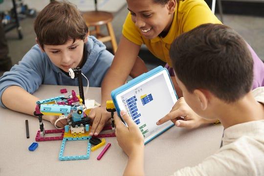 Estudiantes montan un SPIKE Prime, que consiste en un soporte con forma rectangular, que cabe en la palma de la mano, y al que se le pueden añadir diferentes ladrillos de LEGO con los que ir montando figuras