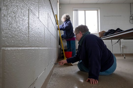 Chris Danner, forward, works to chip old paint off a wall while Jeanne Mackay cleans a windowsill Tuesday, April 2, 2019 in one of the rooms at the Friends of the St. Clair River office in Port Huron.