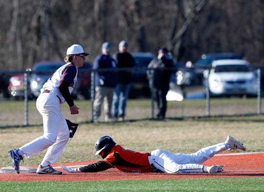 Marlboro's Christian Diorio slides into third base as Arlington's Jack Sims covers during Monday's game on April 1, 2019.