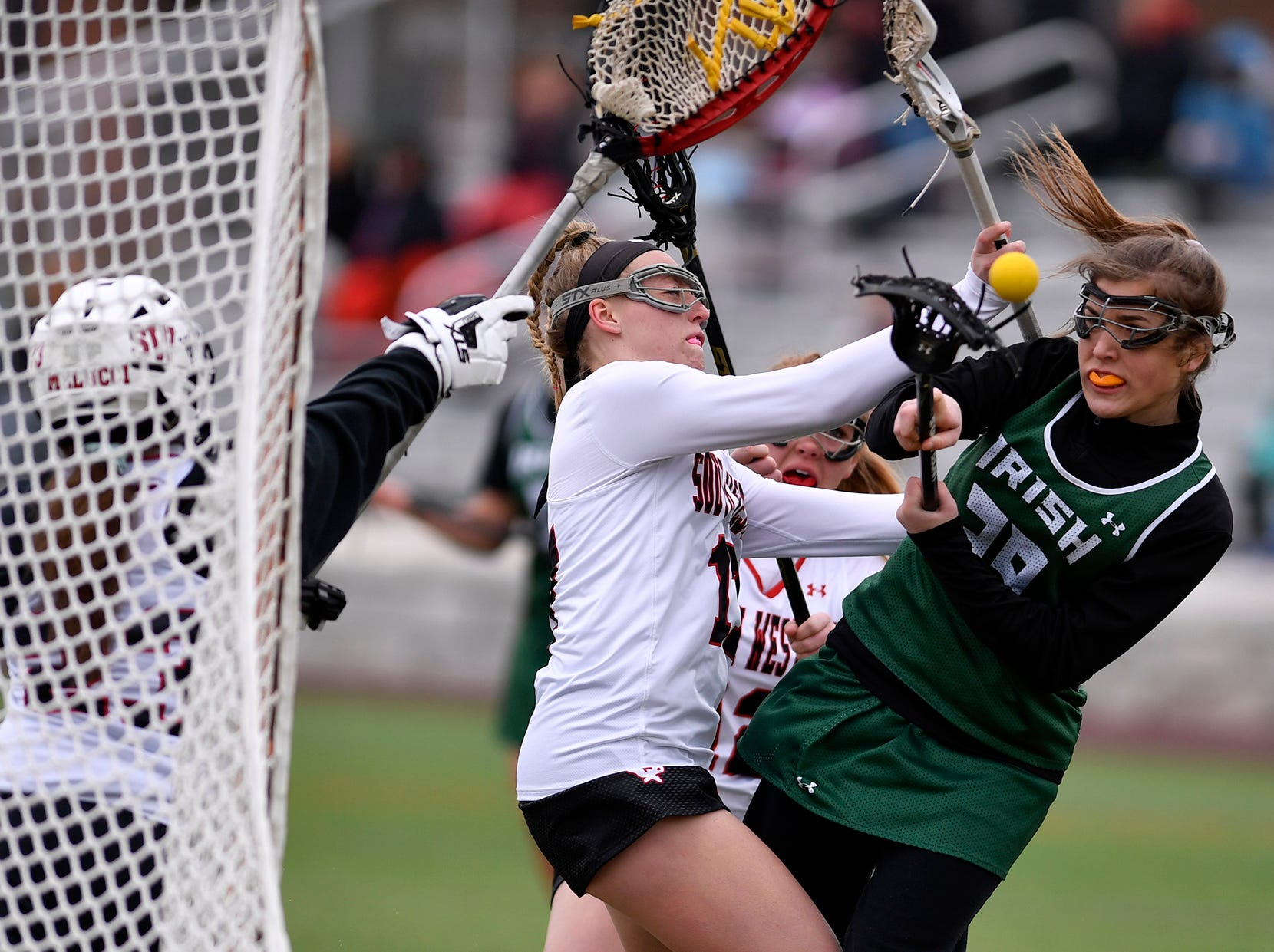 York Catholic's Gracy Gulley is cross checked by Libby Benzing of South Western, Tuesday, April 2, 2019.John A. Pavoncello photo