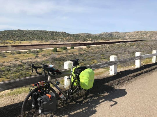 Dave Watkins takes a photo with his bicycle during his journey, at the United States, Mexico border fence in the background on Day 2 of his ride.