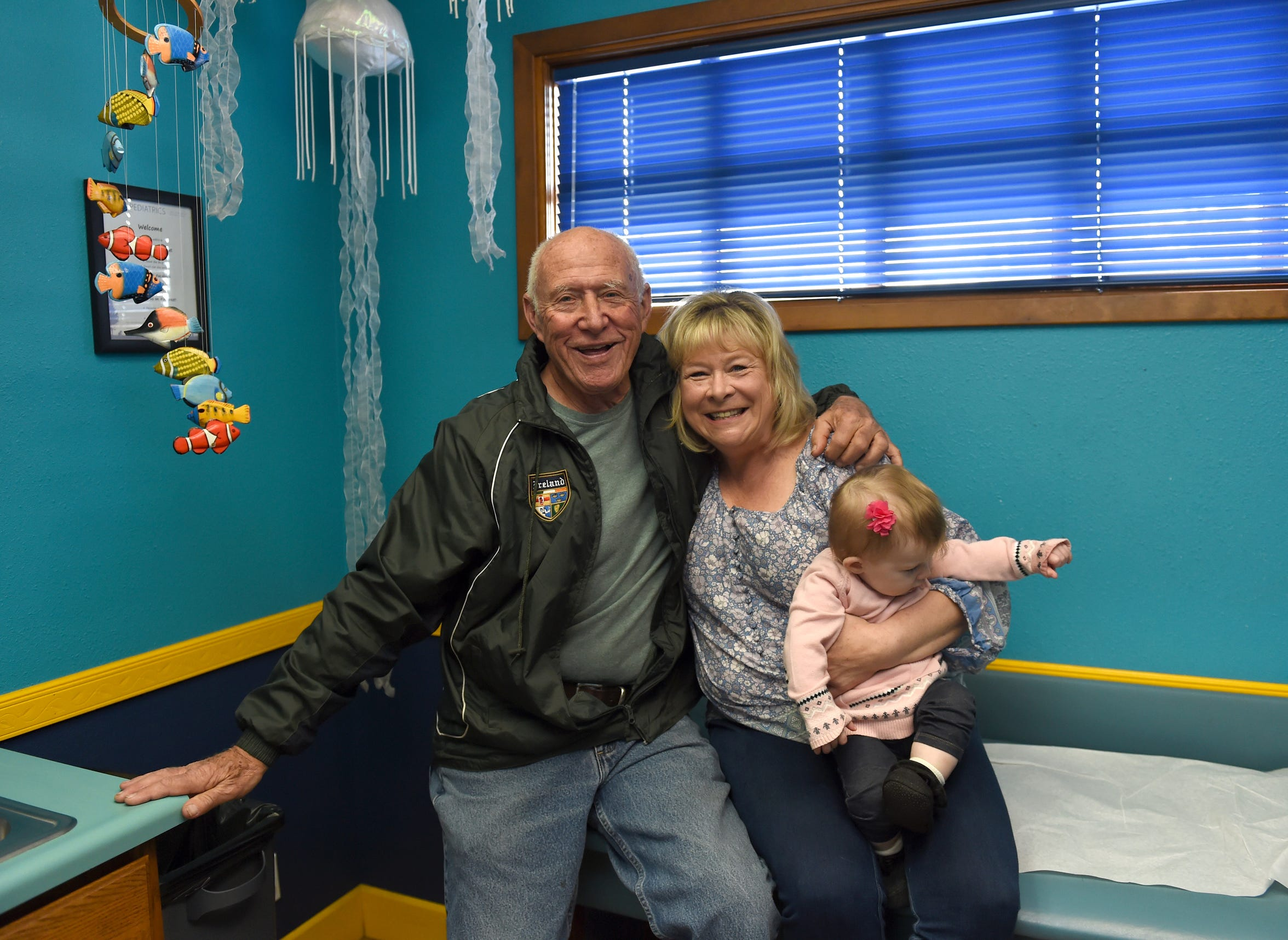 Dr. Patrick Colletti poses for a photo with his long-time nurse Jane Prescott, who is holding her granddaughter Blair Gutierrez, 10 months. The three are at Aspen Pediatrics in Reno. Colletti is retiring after 50 years of working to keep children healthy in Northern Nevada.