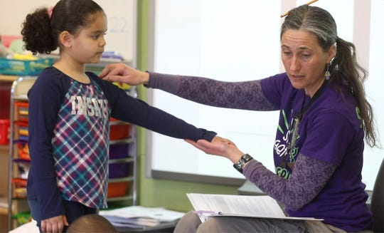 Jamie Schenk uses Chaliyah Muktarian's arm and does a movement with her fingers, to go over the sound of letters with Chaliyah and a small group of other students.  Schenk is a kindergarten teacher at World of Inquiry.