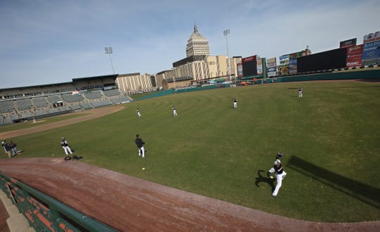 Pitcher Preston Guilmet, right, throws deep in the outfield as the Rochester Red Wings take to Frontier Field for a light workout during media day at the ballpark Tuesday, April 2, 2019.