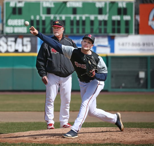 With pitching coach Stu Cliburn looking on, left, starting pitcher Kohl Stewart throws from the mound as the Rochester Red Wings take to Frontier Field for a light workout during media day at the ballpark Tuesday, April 2, 2019.  Stewart will get the ball and start for the Wings season opener on Thursday against Lehigh Valley.