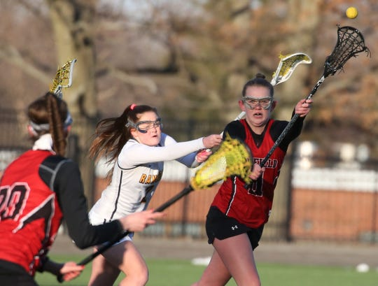 Penfield's Nina Nesselbush, right, passes to teammate Elisa Faklaris, left, as Spencerport's Erin Coykendall presses.