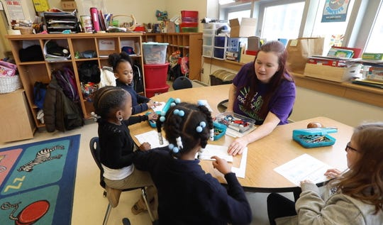 Tray'Cee Jackson and Journey Cochran, work on their kindergarten assignment while teacher Megann Johnson answer's Justice Jackson question.  Waiting to ask Johnson a question is Kaliana Affronti.  The kindergartners are in an integrated co-taught kindergarten class at World of Inquiry.  The 'ICOT' is where a special education teacher is paired with a general education teacher and they co-teach all the students.  Johnson is a special education teacher.