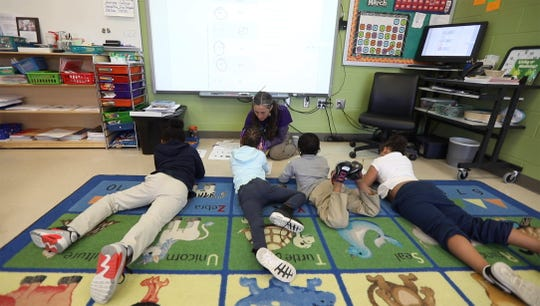 Jamie Schenk works with a small group of her kindergarten class on writing words.  The class was broken up into small groups with students rotating through teachers and independent work.  The World of Inquiry class is an integrated co-taught class where both the general education and special education teacher teach all students in the class.  Schenk is a general education teacher.