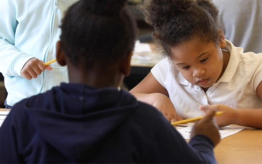 Layanna Lindsay and Kardae Porter, back to camera, write on their worksheets in their kindergarten class at World of Inquiry.  Standing, half out of the frame is Amor Perkins.