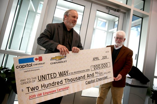 Ron Hays, executive director of United Way of the Mid-Willamette Valley, accepts a check with the help of Mayor Chuck Bennett of $200,000 raised by Capitol Auto Group employees, in the Chevrolet lobby of Capitol Auto Group in Salem on April, 2, 2019.