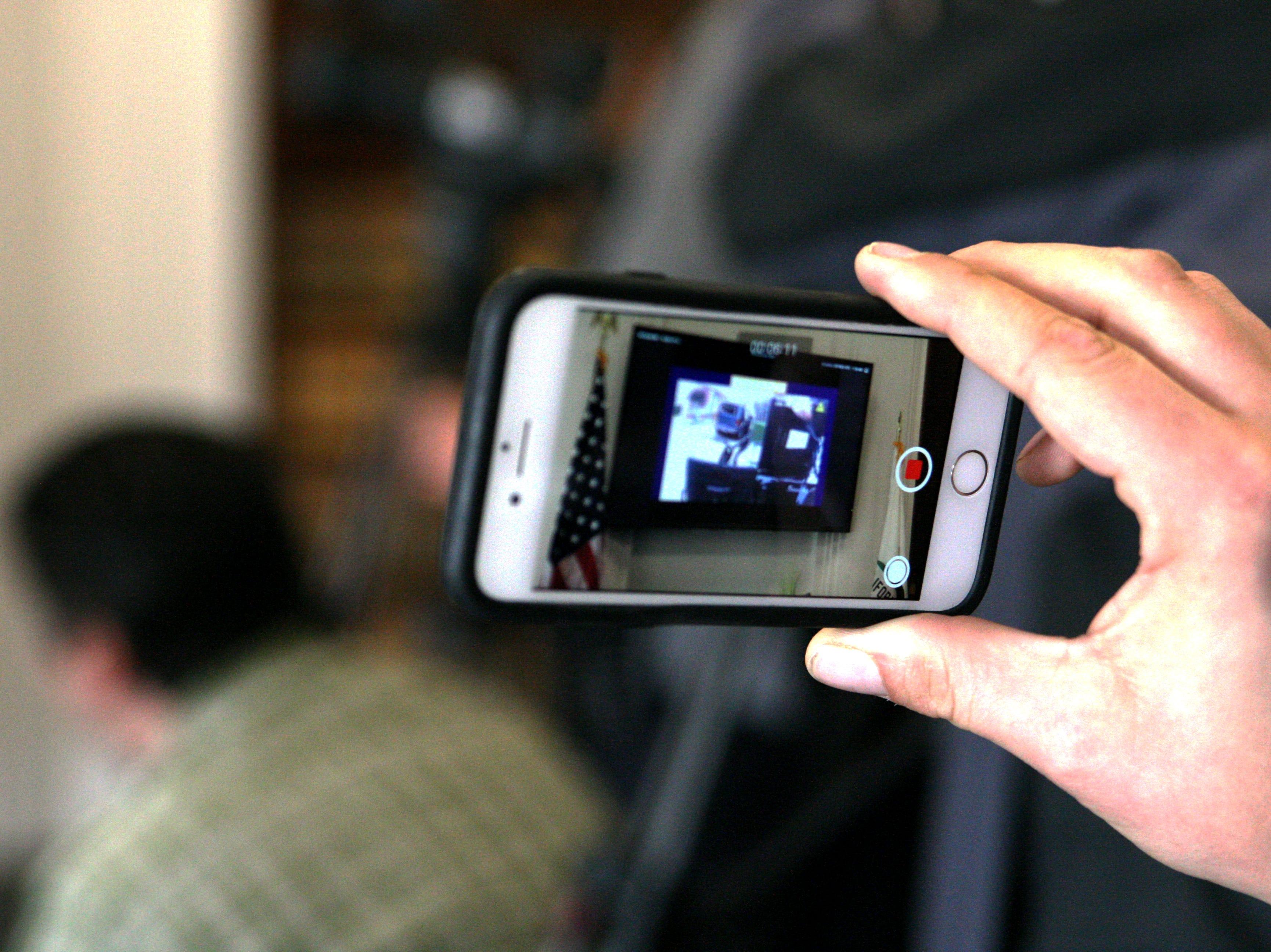 Reporter Joe Szydlowski holds up his phone, recording the slowed-down footage of the shooting death of Brenda Mendoza, aka Brenda Rodriguez. April 2, 2019.