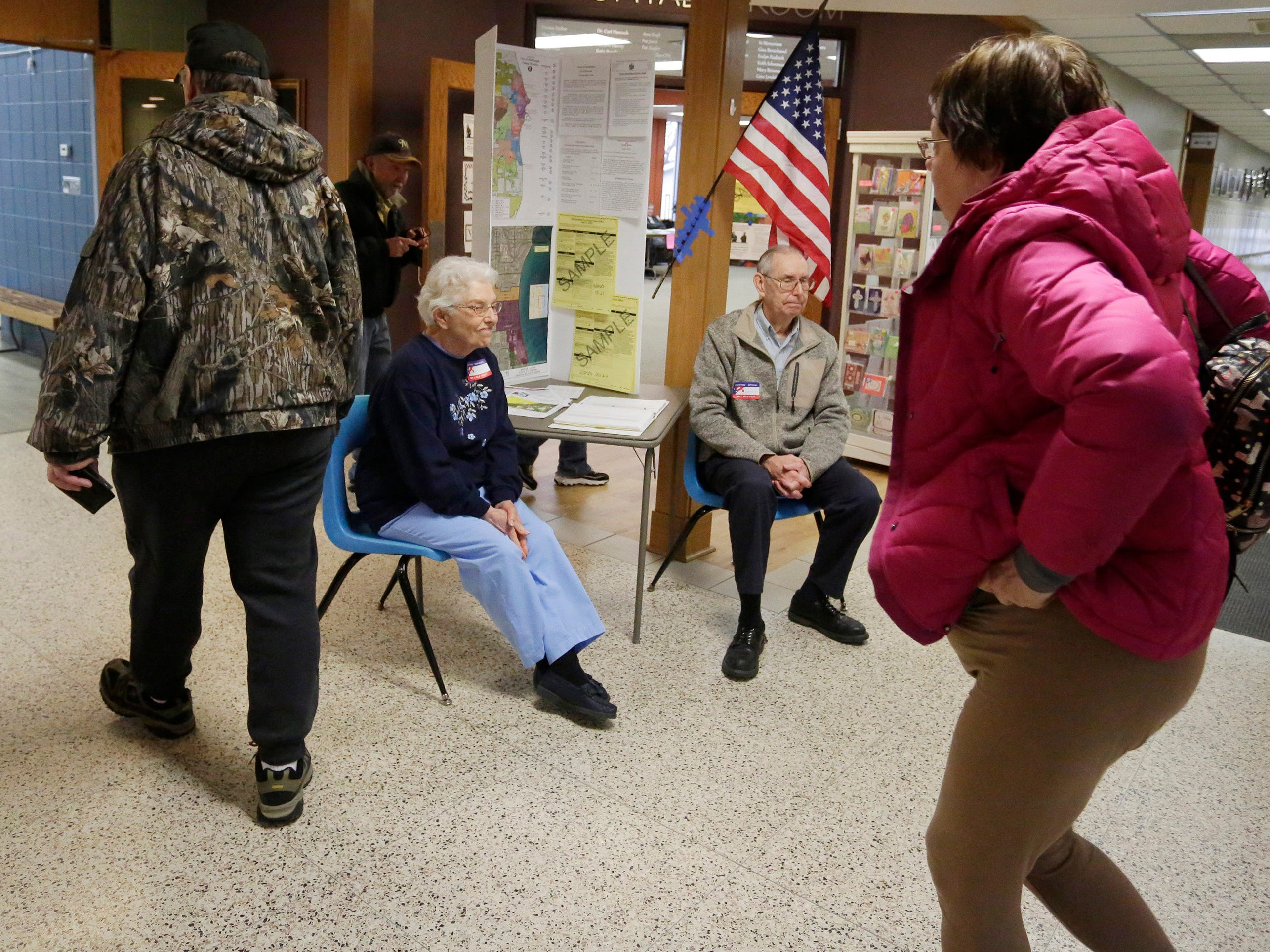 Poll workers Laverne Mueller, left, and Jerry Smith, right, wait to help voters at the Bethany Reformed church polls, Tuesday, April 2, 2019, in Sheboygan, Wis.