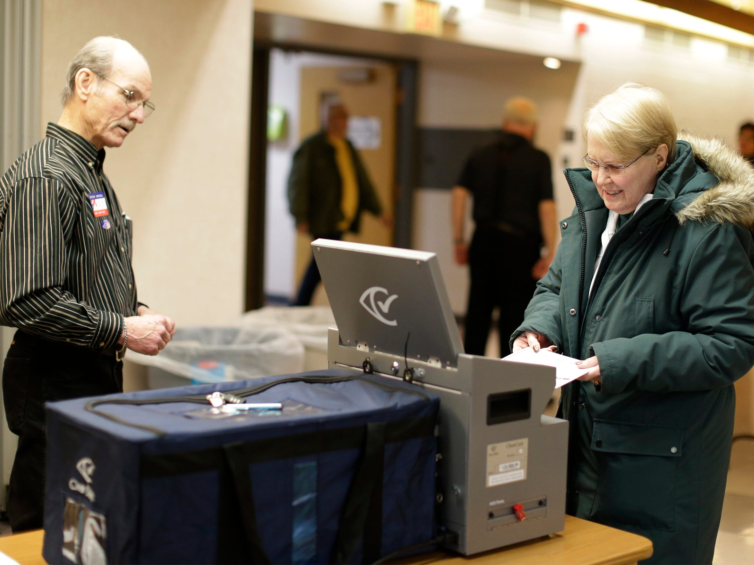 Linda Eickhoff, right, casts her ballot by poll worker Jim LaCroix, left, at First United Lutheran polls, Tuesday, April 2, 2019, in Sheboygan, Wis.