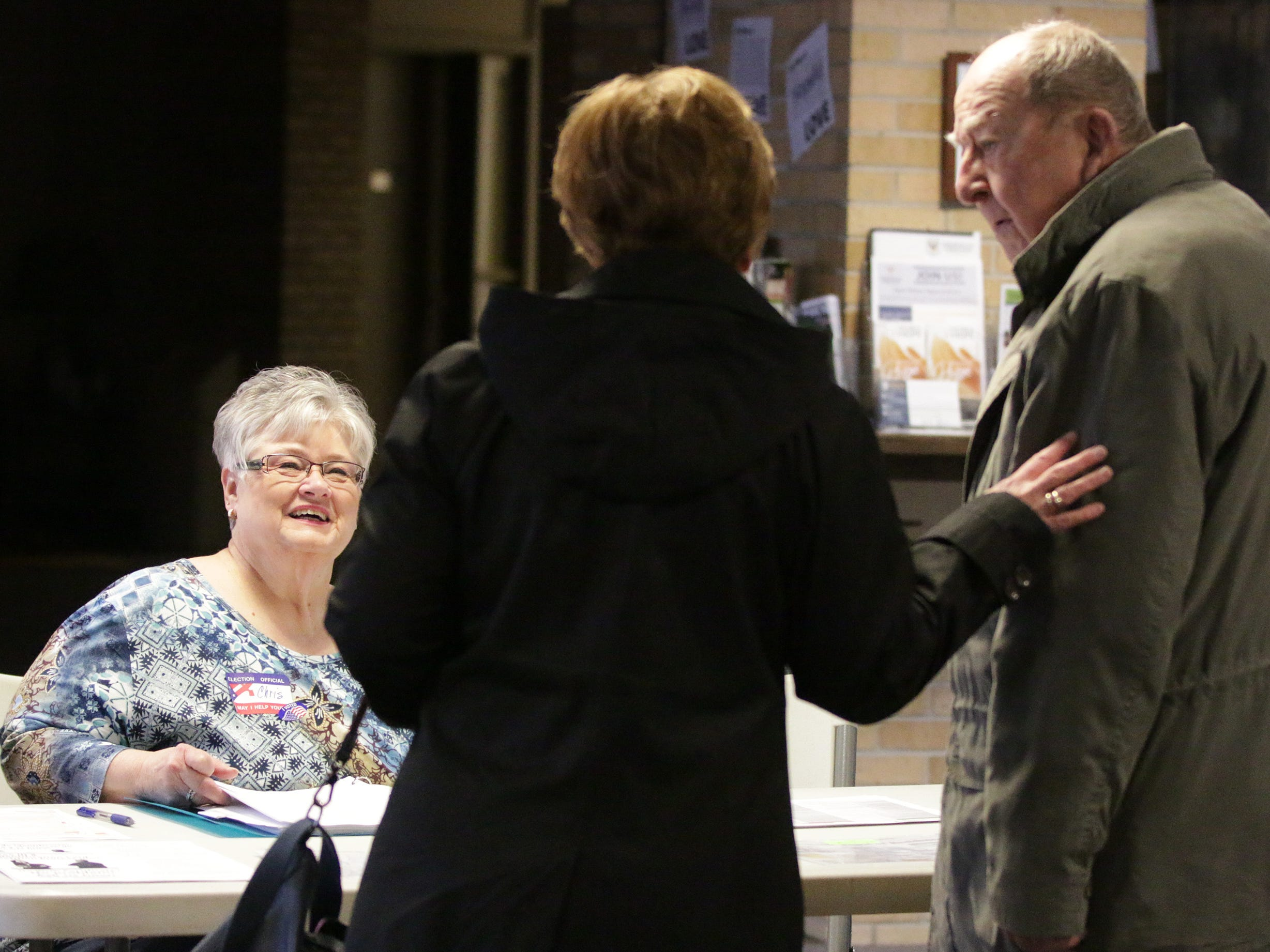 Poll Worker Chris Wieck smiles as she talks to voters following their vote at the Bethany Reformed Poll, Tuesday, April 2, 2019, in Sheboygan, Wis.