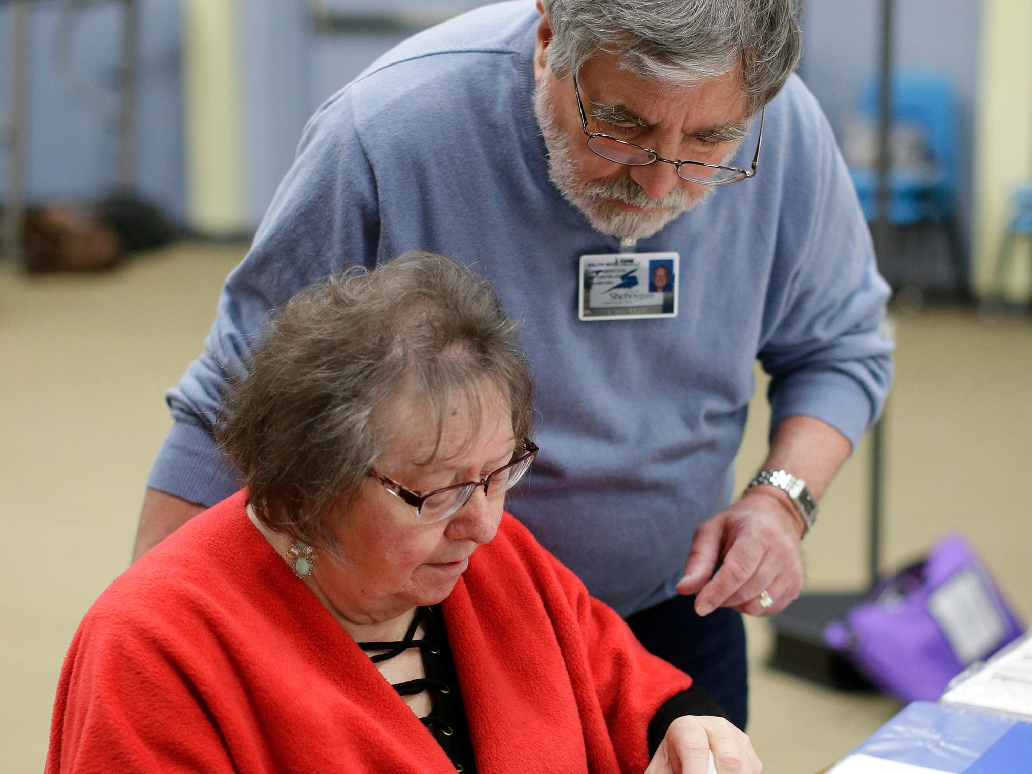 Poll worker Agnes Soerens looks over election paperwork with poll supervisor Ralph Maffongelli at the Senior Activity Center poll, Tuesday, April 2, 2019, in Sheboygan, Wis.