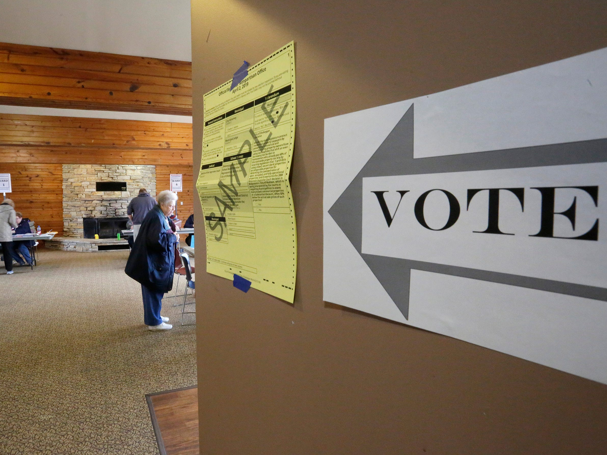 A sign points to voting at the Quarryview Center, Tuesday, April 2, 2019, in Sheboygan, Wis.