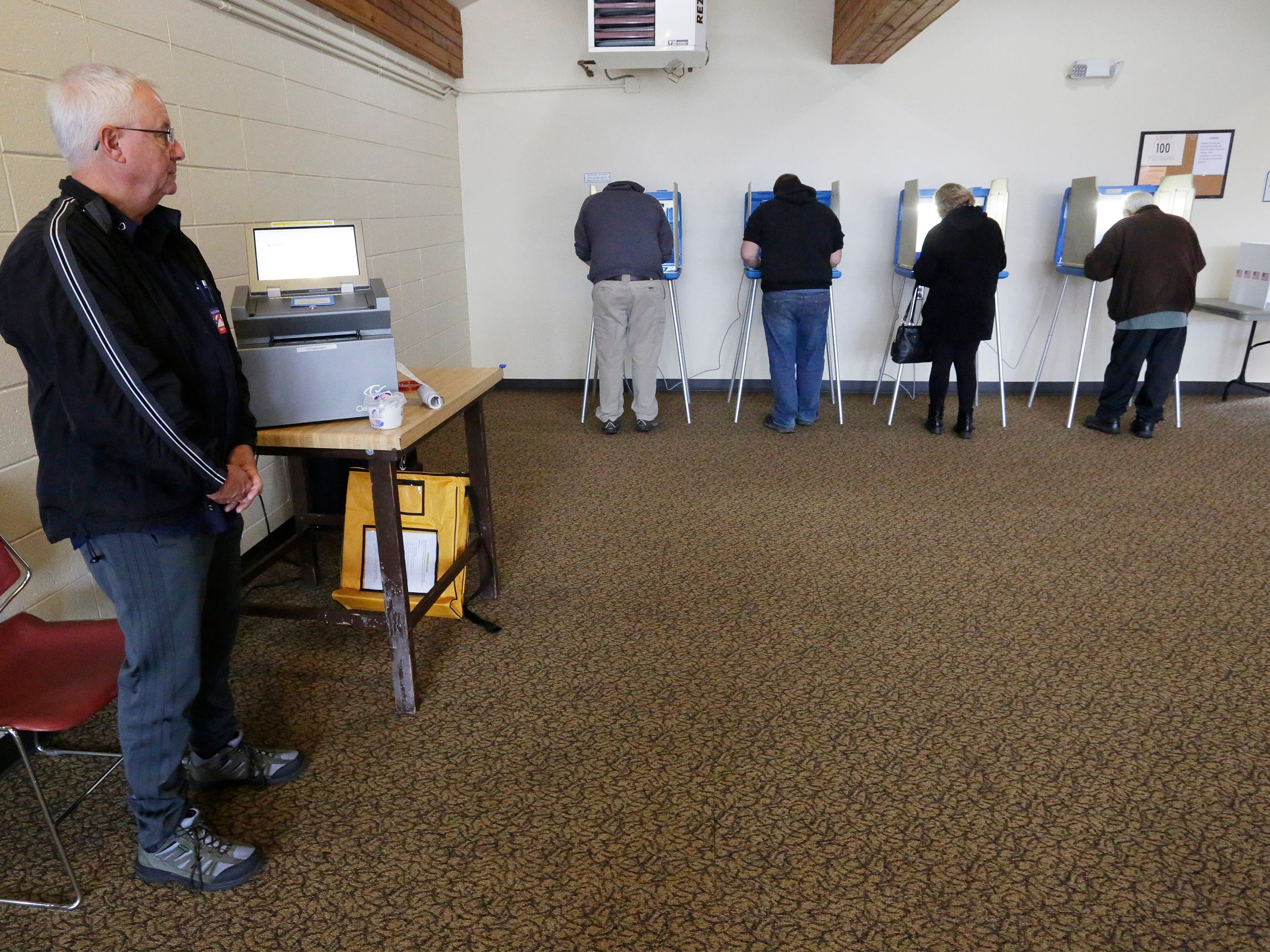 Poll worker Dan Dever, left, waits for voters to complete their ballots at the Quarryview Center polls, Tuesday, April 2, 2019, in Sheboygan, Wis.