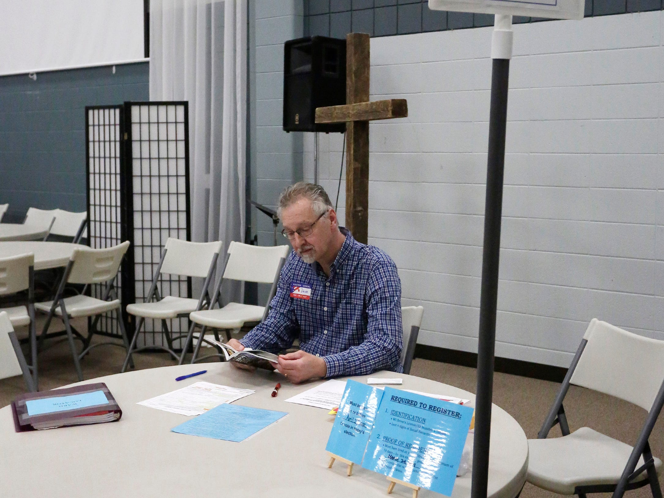 Poll worker Dave Derus waits for a voter to register at the Bethany Reformed polls, Tuesday, April 2, 2019, in Sheboygan, Wis.