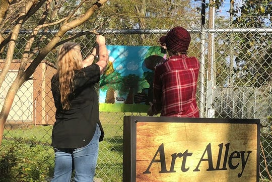 Heather Clark (left) and a volunteer install the student artworks in Art Alley.