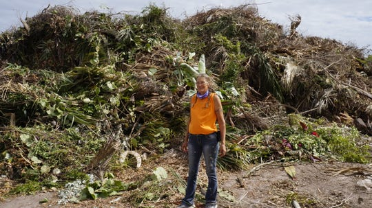 Landfill ground spotter Jami Moore in front of yard debris.