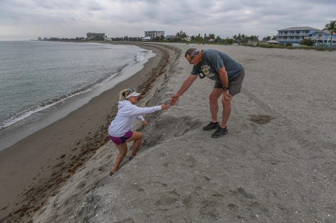 "Patty Schilling (left) gets help from her husband Roland while climbing the eroded dune as the couple from Nettles Island were out for a walk before coffee on Tuesday, April 2, 2019, at Fort Pierce Beach, just south of the Fort Pierce Inlet. ""It's unbelievable, it's the deepest cut into the ocean I've ever seen. It's really steep,"" Patty Schilling said. ""It's amazing what the ocean can take away."""